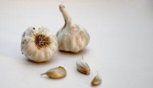 garlic bulb and garlic on white surface